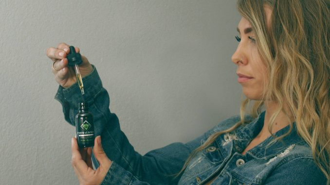 אישה מחזיקה בקבוקון שמן CBD