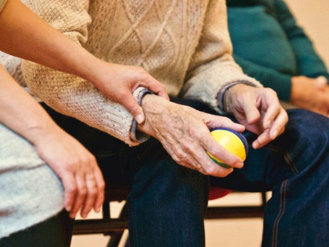 אישה אוחזת ביד של אדם מבוגר בגיל השלישי